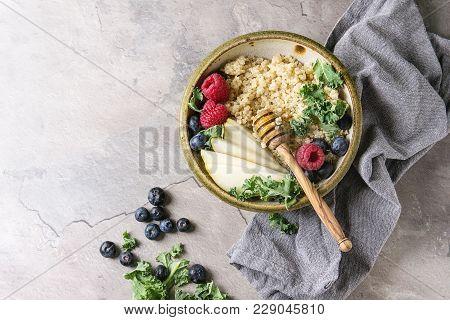Vegan Quinoa Porridge With Kale, Strawberries, Blueberries, Sliced Pear, Honey On Dipper In Bowl Wit