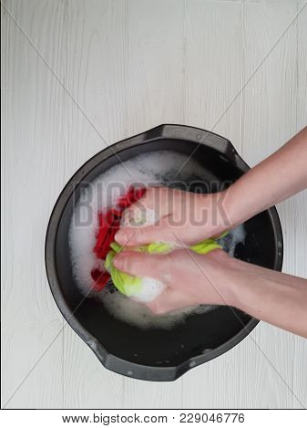 Hands Washing Clothes In Basin Wooden Background
