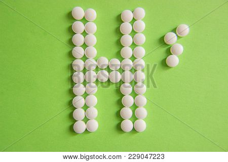 Sign H, For Hospital, Made By White Pills On Green Background, Close Up