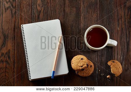 Porcelain Cup Of Black Tea Or Earl Grey With Chocolate Chips Cookies, Blank Workbook And A Yellow Pe