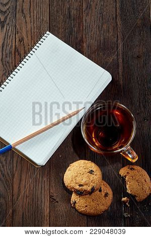 Transparent Glass Cup Of Black Tea Or Earl Grey With Chocolate Chips Cookies, Blank Workbook And A Y