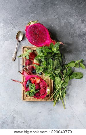 Vegan Fruit Salad With Berries And Mint Served In Pink Dragon Fruit With Ingredients Above On Wooden