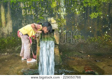 Lao Cai, Vietnam - Sep 7, 2017: Ethnic Minority Child Drink Water From Small Spring Downstream From
