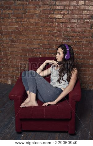 Sad Teenager Girl Listening To Music On Headphones Cringing Herself In An Old Chair In An Abandoned