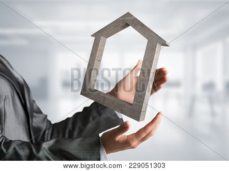 Business Woman In Black Suit Keeping Stone House Symbol In Hands With Office View On Background. Mix