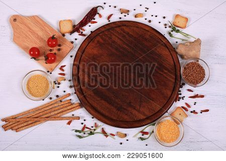 Food Frame Around Brown Round Cutting Board On White Wooden Table. Organic Food For Healthy Nutritio
