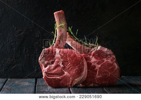 Raw Uncooked Black Angus Beef Tomahawk Steaks On Bones Served With Rosemary Over Dark Wooden Plank T