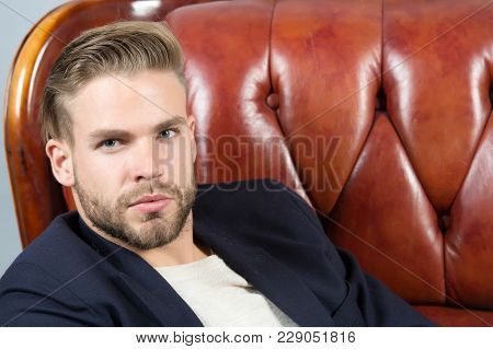 Macho Sit In Brown Leather Armchair. Man With Unshaven Face, Blond Hair, Haircut, Beauty. Barber Sal