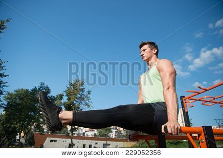 Sportsman Hold Raised Legs Straight On Parallel Bars, Workout. Man Athlete Training On Fresh Air Out