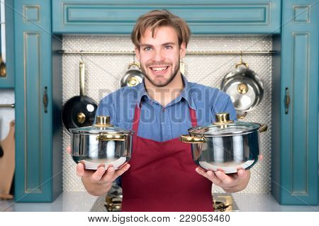 Kitchen Pots In Hands Of Happy Man In Red Apron. Kitchen Tool, Utensils, Kitchenware, Set.