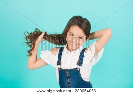 Girl Hold Long Hair On Blue Background. Child Smile With Healthy Brunette Hair. Haircare, Hairstyle