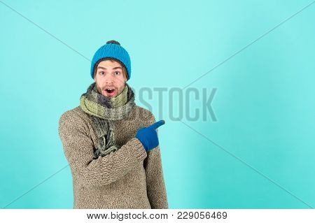 Macho in warm hat, sweater, scarf, fashion. Surprised man point finger in glove. Winter fashion, style, trend. Presenting product, copy space, bum poster