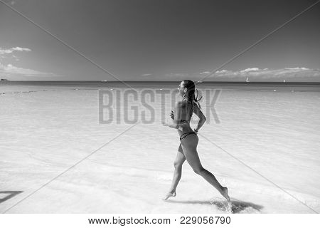 Woman In Bikini Running On Beach With White Sand, Turquoise Sea Or Ocean Water And Blue Sky On Sunny