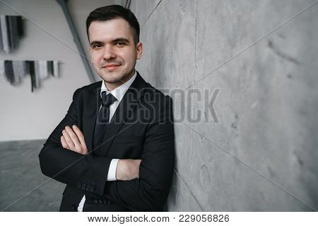 Portrait Of A Young Successful Man In A Black Suit Against A Gray Concrete Wall In Loft Style. Proud