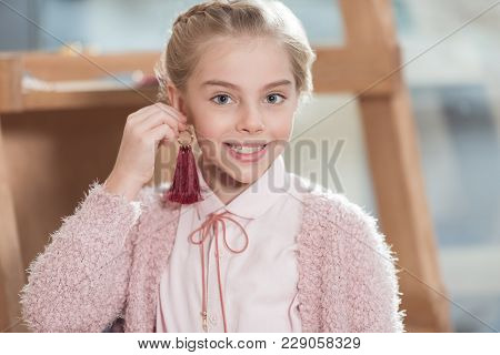 Smiling Child Looking At Camera While Holding Suspension Near Her Ear