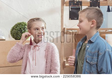 Smiling Girl Looking At Boy While Holding Suspension Near Her Ear At Store