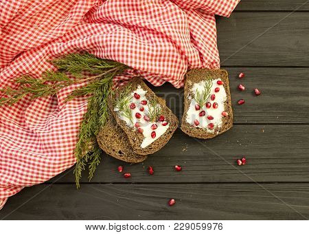 Black Bread With Grenades Berries On A Black Wooden Background. Christmas Food, Christmas Decoration