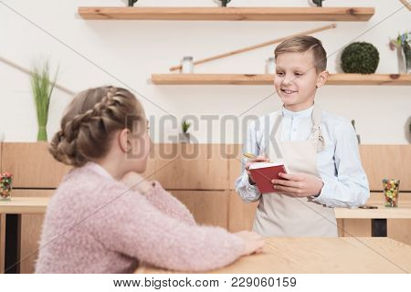 Smiling Little Waiter Making Notes In Notepad Against Child At Cafe