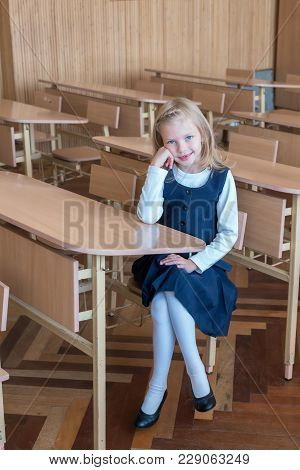 First Grade Student At School At The Desk. Emotions Of Schoolgirls