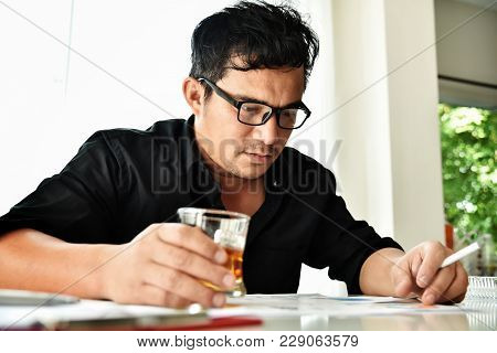 Alcohol Addicted Businessman Is Holding Cigarette And Whiskey Glass While Working. Sad Depressed Pat