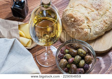 Bowl With Different Kind Of Olives, Glass Of Wine, Cheese And And Fresh Bread Ciabatta On The Wooden