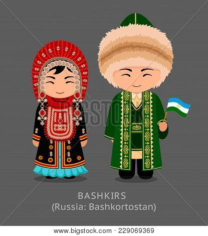 Bashkirs In National Dress With A Flag. Man And Woman In Traditional Costume. Travel To Russia (repu