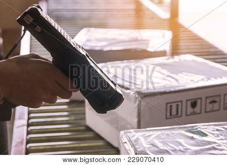 Hand Of Warehouse Worker Holding Barcode Scanner With Scanning Laser On Package Boxes.