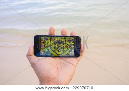 Malaysia, Terengganu July 2017 : Hand Holding A Cellphone Playing Supercell's Clash Of Clan At The B
