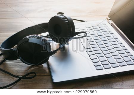 Headphones And Laptop Keyboard On Wooden Board. Closeup