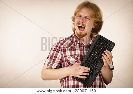 Nerd Geek Young Adult Man Playing Video Games Holding Computer Keyboard. Being Addicted To Gaming Co