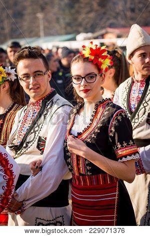 Pernik, Bulgaria - January 26, 2018: Couple Dancers In Bulgarian Folklore Costumes Hold Arms During