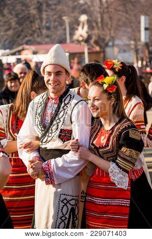 Pernik, Bulgaria - January 26, 2018: Couple Young Dancers In Bulgarian Folklore Costumes Hold Arms A