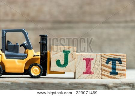 Toy Yellow Forklift Hold Letter Block J To Complete Word Jit (abbreviation Of Just In Time)on Wood B