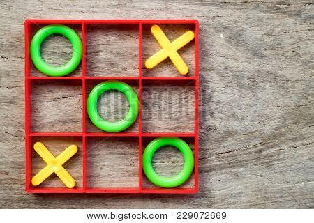 Tic-tac-toe Board Game With Green O And Yellow X In Red Frame On Wood Background
