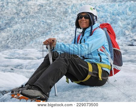 Young Woman Climber Sitting With An Ice Pick In Her Hand On A Falljokull Glacier (falling Glacier) I