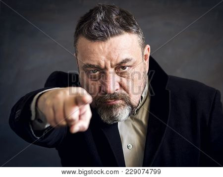 Angry Bearded Man In A Black Suit Point A Finger At You. Copy Space. A Gesture Of Choice. Dark Backg