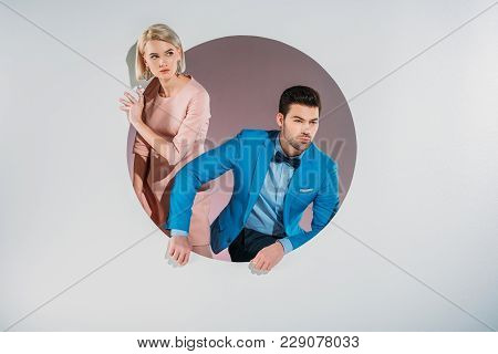 Beautiful Fashionable Young Couple Peering Out Hole On Grey