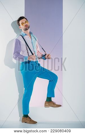 Handsome Stylish Young Man In Suspenders And Eyeglasses Standing In Aperture On Grey