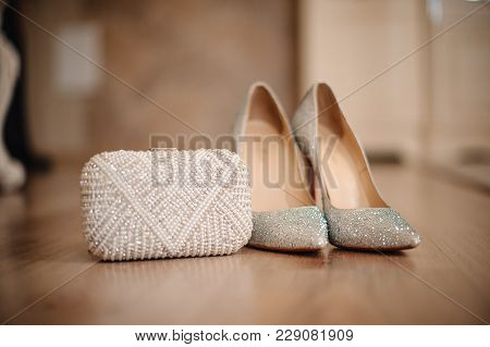 Graceful Shoes Of The Bride, Studded With Shiny Pebbles, Stand On The Beige Floor Next To A Small Wh