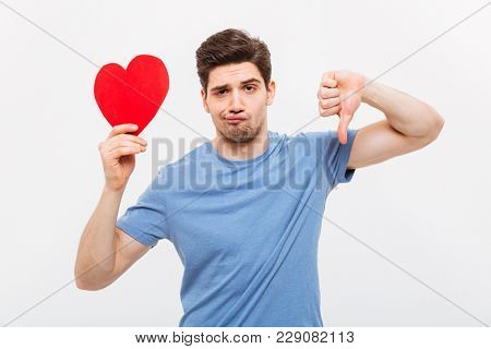Displeased man in t-shirt holding paper heart and showing thumb down while looking at the camera over grey background