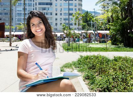 Beautiful Brazilian Female Student Learning Outdoors In Summer In City