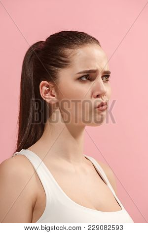 Beautiful Female Three-quarters Portrait. Isolated On Pink Studio Backgroud. The Young Emotional Sad