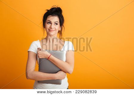 Portrait of fascinating woman with trendy hairstyle hugging modern silver laptop and looking aside with brooding sight over yellow wall copy space
