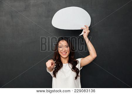 Smiling female asian holding blank speech bubble above her head and pointing finger on camera isolated over dark gray background