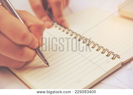 Female Hand Holding Silver Pen Closeup. Doing Homework.writing Make Note
