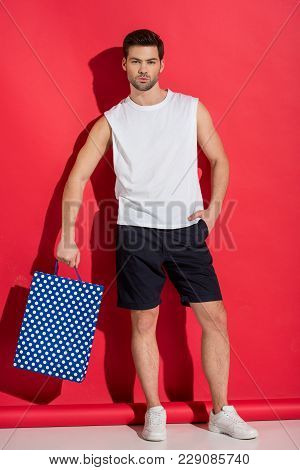 Full Length View Of Handsome Young Man Holding Shopping Bag And Looking At Camera On Pink