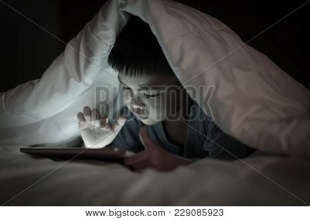 Asian Boy Using Tablet Screen While Lying On Bed Under White Blanket, In The Bedroom At Night, Brigh