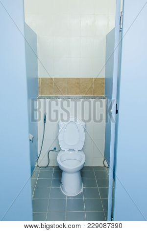 White Ceramic Flush Toilet In Toilet Room. Modern Toilet Bowl In A Men Bathroom