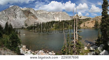 Snowy Mountain Range, Medicine Bow National Forest, WY. Short hike off scenic byway with gorgeous mountains, Lake Marie, blue sky, white cumulus clouds, trees, rocks, stones.