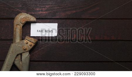 Pipe Wrench Compresses A Piece Of Paper With An Inscription Fake News.
